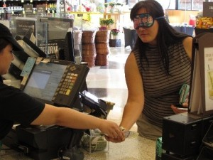 person wearing sleepshades receives change from barista